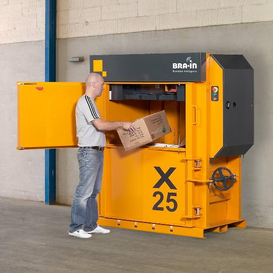 yellow cardboard baler with man inserting cardboard box. Up against a concrete warehouse wall
