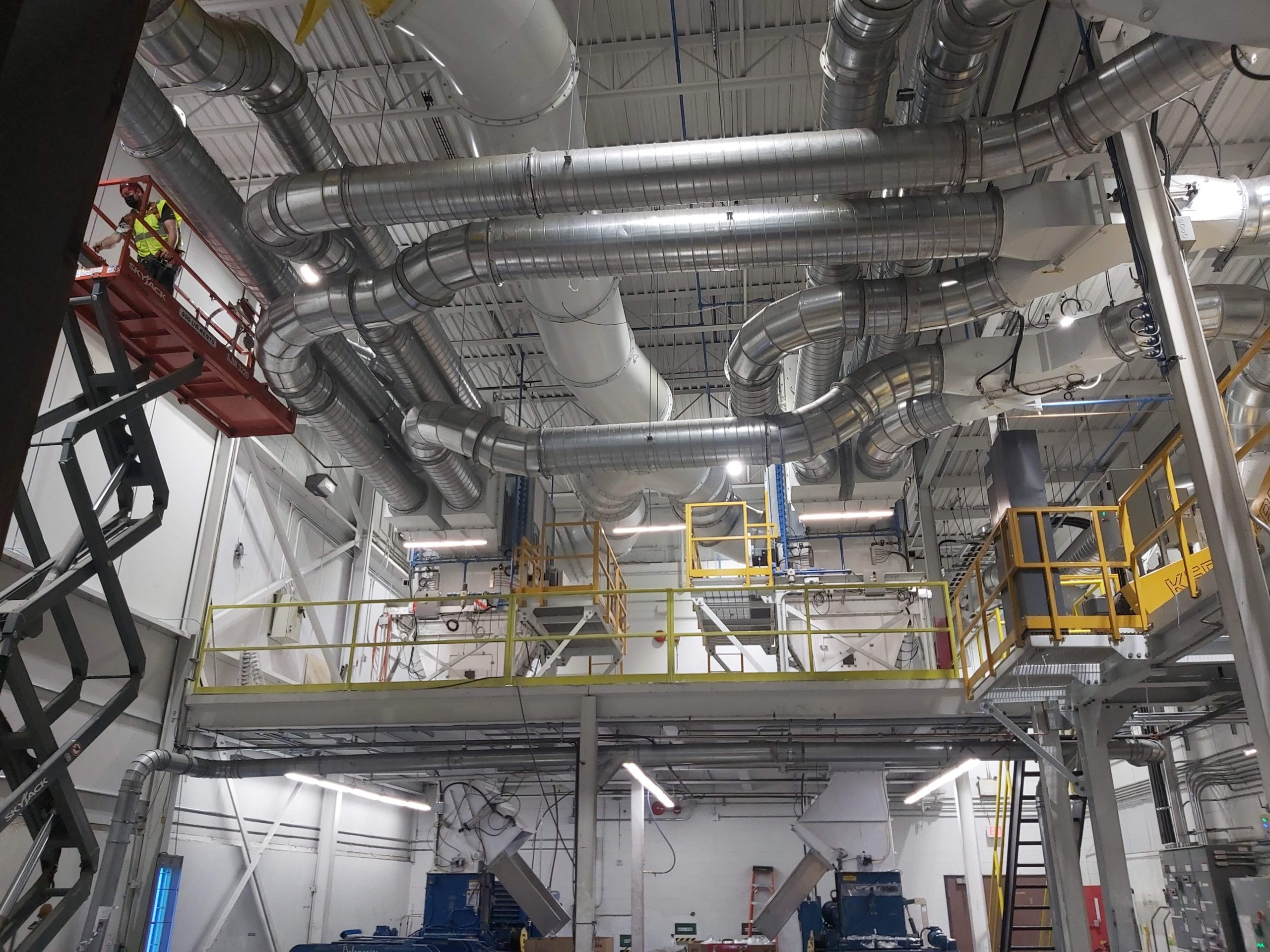 Ductwork inside a large building with a technician on a scissor lift adding more.