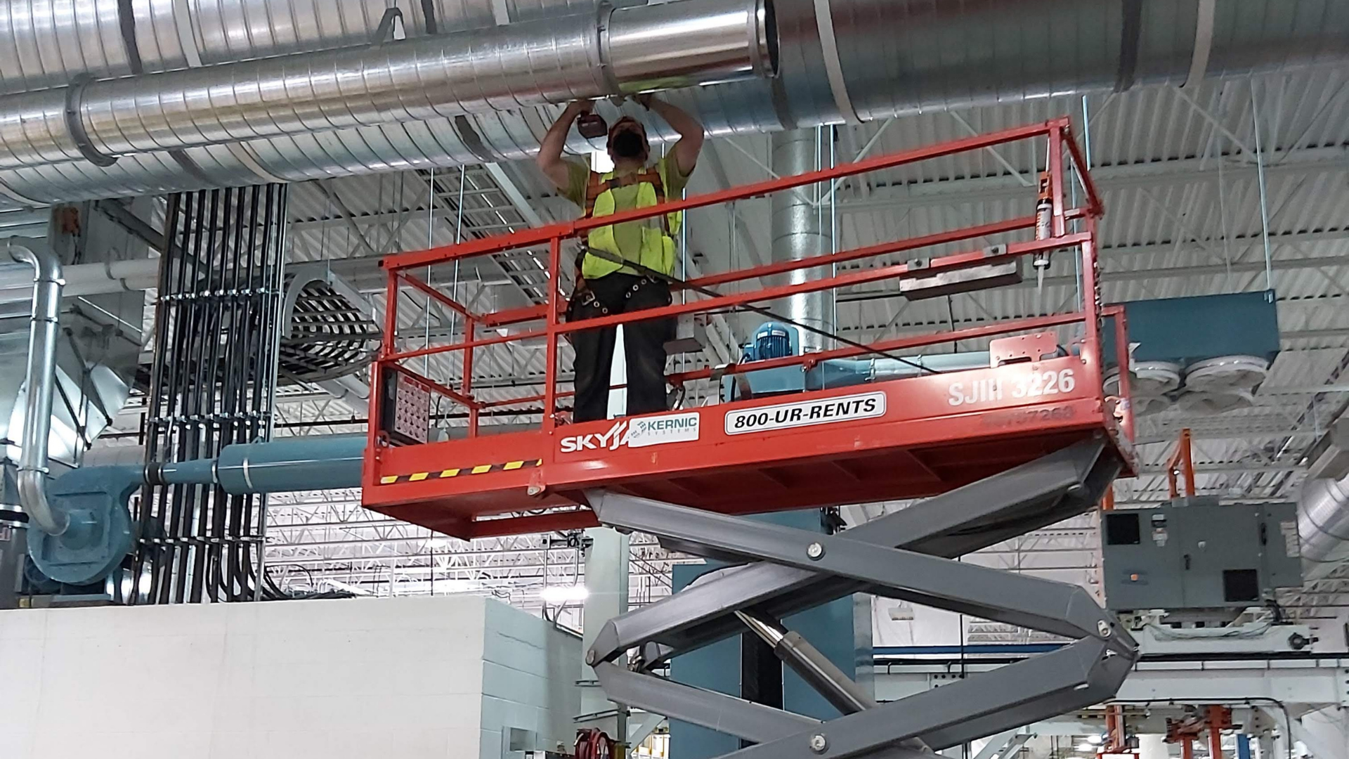 man on a scissor lift installing metal duct