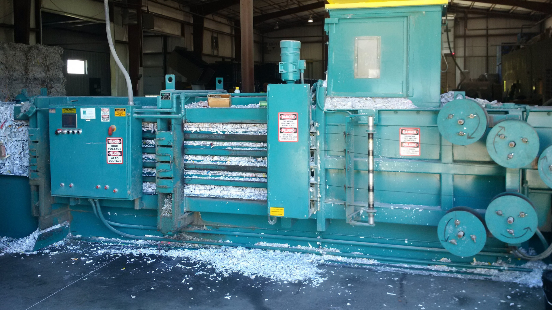 blue baler handling shredded paper in a warehouse
